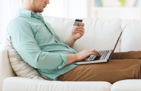technology, shopping, banking, home and lifestyle concept - close up of man with laptop computer and credit card at home photo