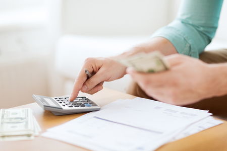 savings, finances, economy and home concept - close up of man with calculator counting money and making notes at home photo