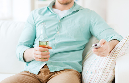 nonalcoholic beer: drinks, television, leisure and people concept - man changing tv channels and drinking beer at home Stock Photo