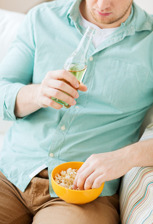 food, drinks, relax, leisure and people concept - close up of man with popcorn and beer sitting on couch at home photo
