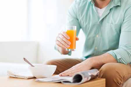 home, news, food, drinks and people concept - close up of man reading magazine and drinking juice sitting on couch at home