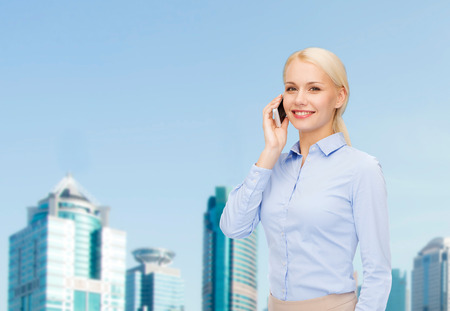 business, technology, internet and education concept - smiling young businesswoman with smartphone over business centre background photo