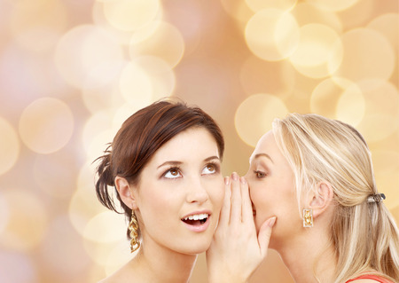 friendship, happiness and people concept - two smiling young women whispering gossip photo