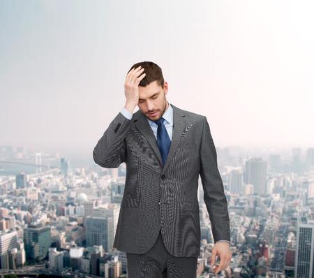 hombre pensando: negocios, la educación y el concepto de oficina - apuesto hombre de negocios que tiene dolor de cabeza sobre el fondo gráfico de divisas más de fondo paisaje urbano