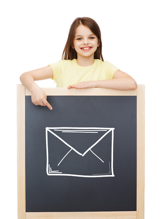 people, childhood, gesture and mail concept - smiling little girl pointing finger to blackboard