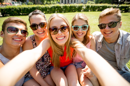 eyewear: friendship, leisure, summer, technology and people concept - group of smiling friends making selfie with smartphone camera or tablet pc in park