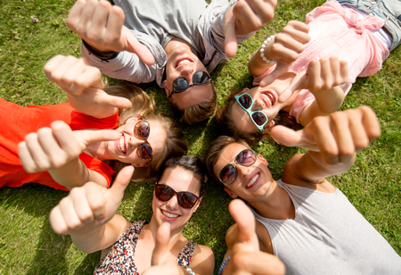 out in town: friendship, leisure, summer, gesture and people concept - group of smiling friends lying on grass in circle and showing thumbs up outdoors Stock Photo