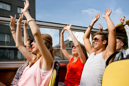 friendship, travel, vacation, summer and people concept - group of smiling friends traveling by tour bus and waving hands photo