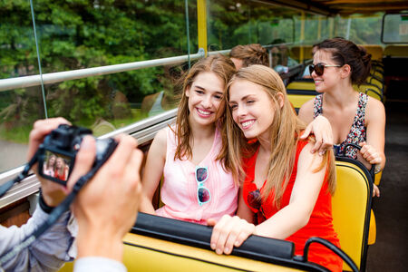 friendship, travel, vacation, summer and people concept - smiling friends with camera traveling by tour bus photo