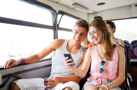 tours: friendship, summer vacation, transport, technology and people concept - smiling couple with smartphone traveling by bus and making selfie
