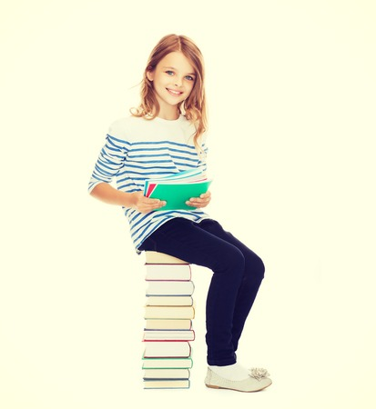 education and school concept - little student girl sitting on stack of books photo