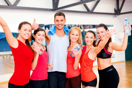gym class: fitness, sport, training, gym and lifestyle concept - group of happy people in the gym with water bottles and towel showing thumbs up and waving hands