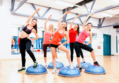 sports coach: fitness, sport, training and lifestyle concept - group of smiling female doing aerobics with half ball,