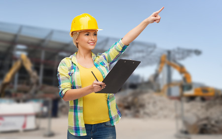 repair, building, construction, maintenance and gesture concept - smiling woman in helmet with clipboard pointing finger photo