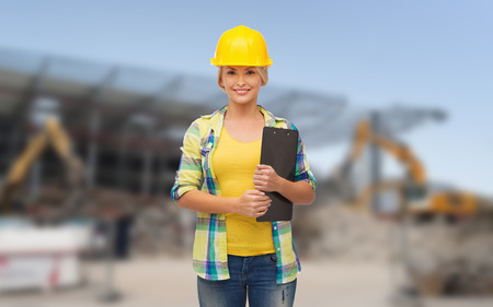 repair, building, construction and maintenance concept - smiling woman in helmet with clipboard photo