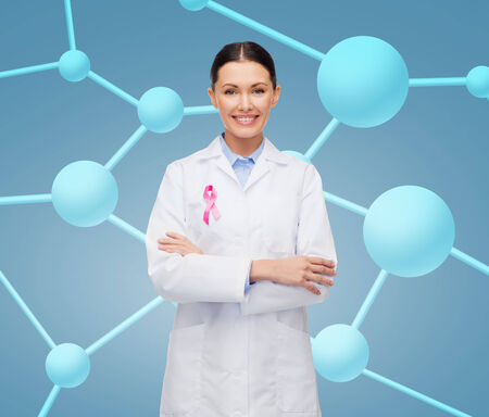 cancer research: healthcare and medicine concept - smiling female doctor with pink cancer awareness ribbon over molecular background Stock Photo