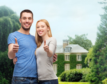 family looking up: couple, gesture and family concept - smiling couple showing thumbs up Stock Photo