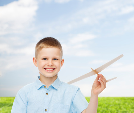 dreams, future, hobby, nature and childhood concept - smiling little boy holding wooden airplane model in his hand over natural background photo