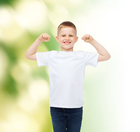 strong arm: advertising, ecology, people and childhood concept - smiling little boy in white blank t-shirt over green background Stock Photo
