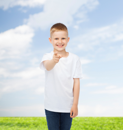 advertising, people, gesture and childhood concept - smiling boy in white blank t-shirt pointing finger at you over natural background photo