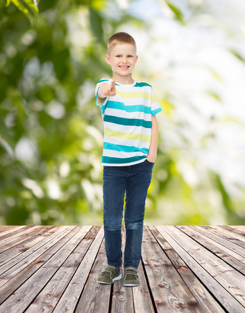 childhood, summer, gesture and people concept - smiling little boy pointing finger at you over plants and wooden floor background photo