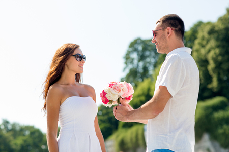 congratulating: love, wedding, summer, dating and people concept - smiling couple wearing sunglasses with bunch of flowers looking at each other in city