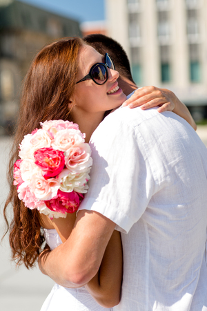 love, wedding, summer, dating and people concept - smiling couple wearing sunglasses with bunch of flowers hugging in city photo