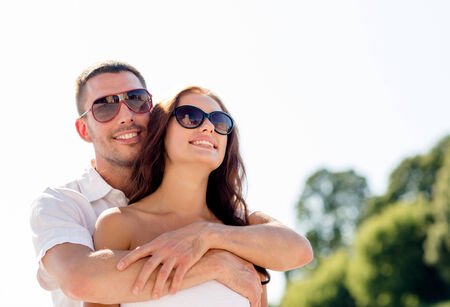 love, wedding, summer, dating and people concept - smiling couple wearing sunglasses hugging in park photo