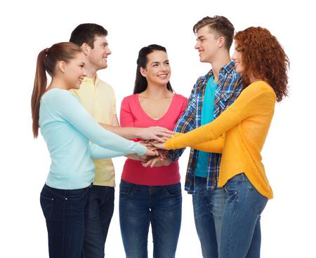 coincidir: la amistad, la juventud y las personas concepto - grupo de adolescentes sonrientes con las manos en la parte superior de uno al otro