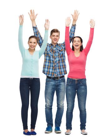 personas saludandose: la amistad, la juventud, saludo y la gente - grupo de adolescentes sonrientes con las manos levantadas Foto de archivo