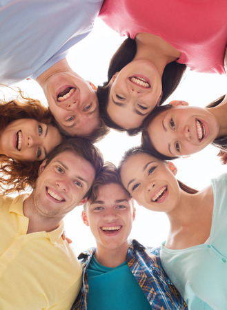 friendship, youth and people - group of smiling teenagers in circle photo