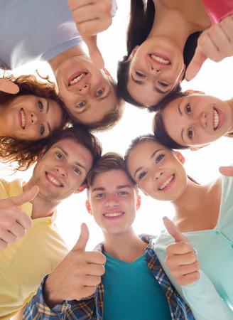 友情、青年、ジェスチャーおよび人々 - サークル表示中笑顔のティーンエイ ジャーのグループの親指します。