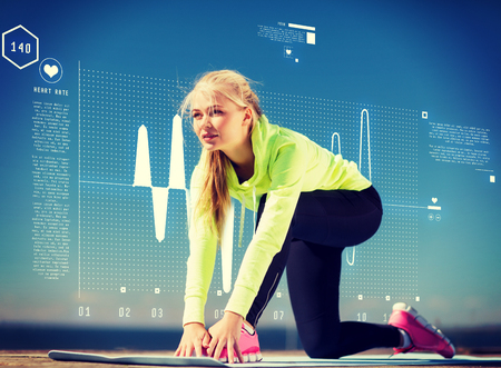 resting heart rate: sport and lifestyle concept - woman doing sports outdoors Stock Photo