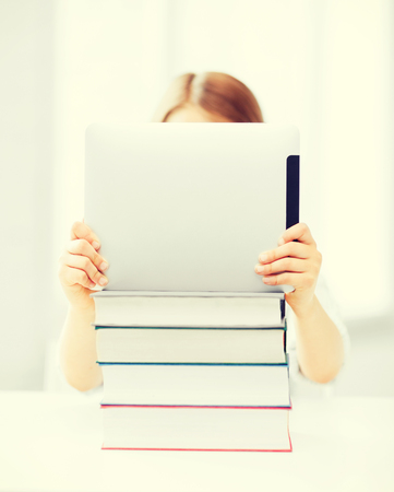 education, school, technology and internet concept - little student girl hiding behind tablet pc and books at school photo