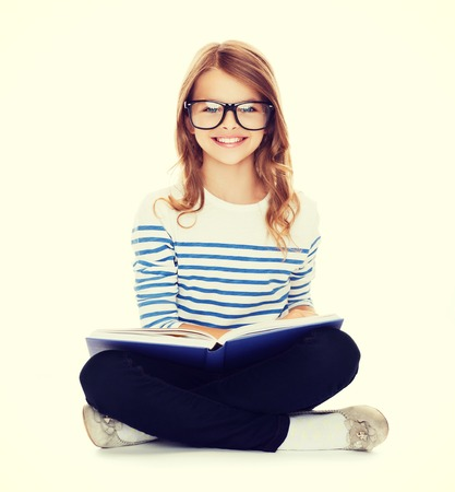education and school concept - smiling little student girl with book and eyeglasses sitting on the floor photo