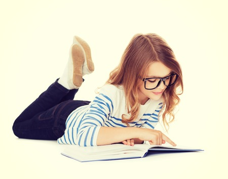 education and school concept - smiling little student girl with book and eyeglasses lying on the floor photo