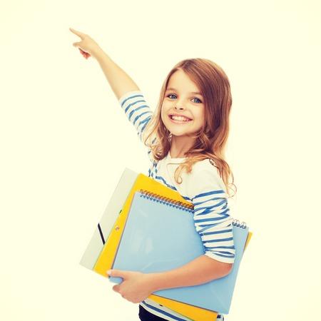 niño empujando: la educación, la escuela y el concepto de pantalla virtual - niña linda con las carpetas de colores apuntando en el aire o la pantalla virtual Foto de archivo