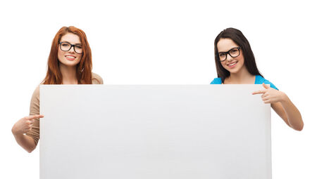 two visions: vision, health, advertisement and people concept - two smiling girls wearing eyeglasses pointing fingers to white blank board