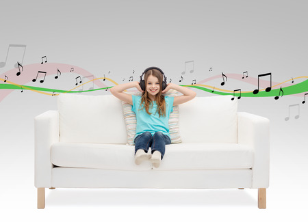 home audio: home, leisure, music and happiness concept - smiling little girl in headphones sitting on sofa Stock Photo