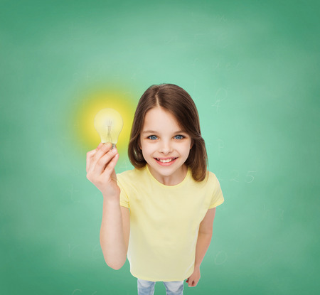 electricity, education and people concept - smiling little girl holding light bulb Stockfoto