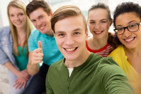 taking: education, leisure and technology concept - five smiling students taking selfie at school