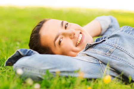 lifestyle, summer vacation, leisure and people concept - smiling young girl lying on grass