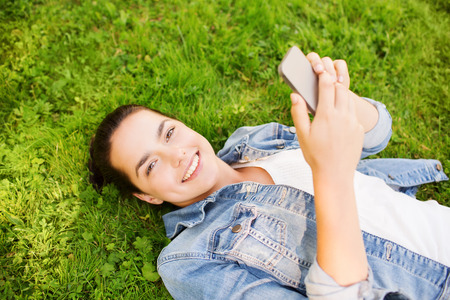 teenage girl happy: lifestyle, summer vacation, technology and people concept - smiling young girl with smartphone lying on grass in park