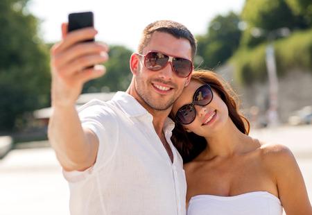 haciendo el amor: amor, boda, el verano, las citas y las personas concepto - sonriente pareja con gafas de sol abrazando y haciendo selfie con el tel�fono inteligente en el parque Foto de archivo