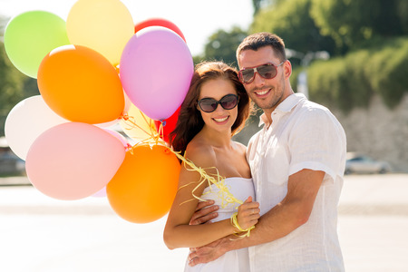 street party: love, wedding, summer, dating and people concept - smiling couple wearing sunglasses with balloons hugging in park