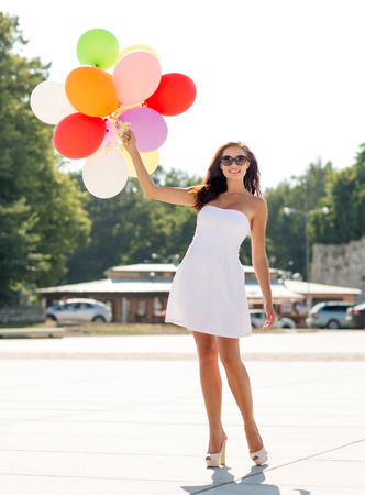 graduation party: happiness, summer, holidays and people concept - smiling young woman wearing sunglasses with balloons in park