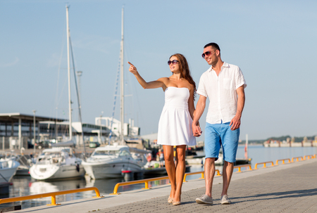 love, travel, tourism and people concept - smiling couple wearing sunglasses walking at harbor and pointing finger photo