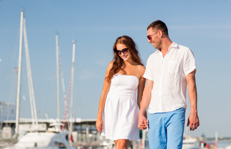 love, travel, tourism and people concept - smiling couple wearing sunglasses walking at harbor photo
