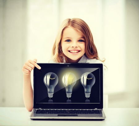 kids laptop: education, school, technology and internet concept - little student girl pointing at laptop pc with light bulbs at school