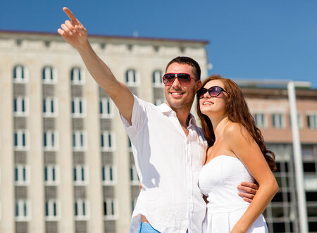 love, travel, tourism, people and friendship concept - smiling couple wearing sunglasses hugging and pointing finger in city photo